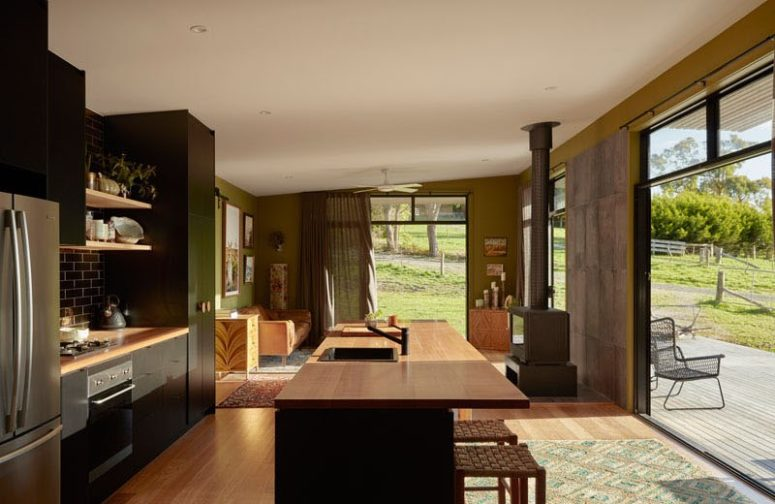 The kitchen and living room are united into one space, with a hearth, a large kitchen island with an eating space and dark kitchen furniture