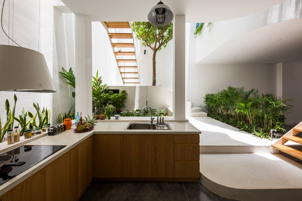 The kitchen is done with sleek cabinets, white stone countertops and greenery all along