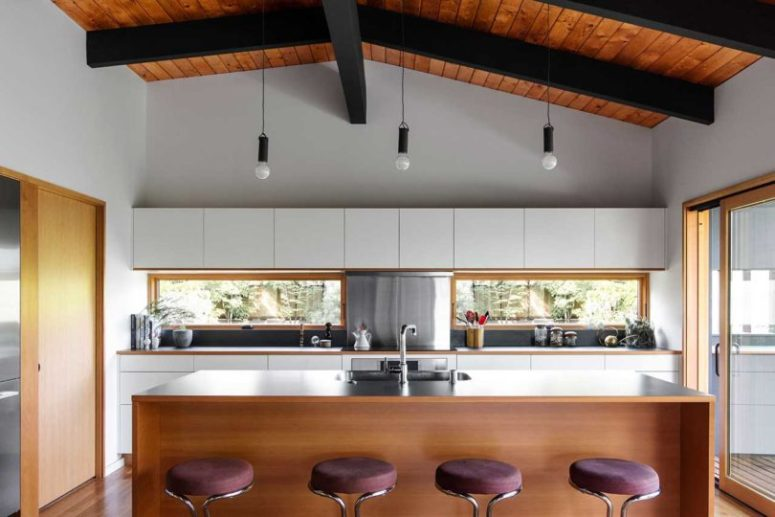 The kitchen is done with white cabinets and dark metal, with a comfortable kitchen island