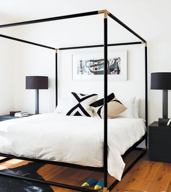 a black canopy bed with gilded corners looks very elegant and chic setting the tone in the bedroom