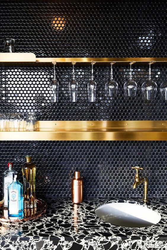a black penny tile backsplash and gold shelves and fixtures make up a very chic and refined combo