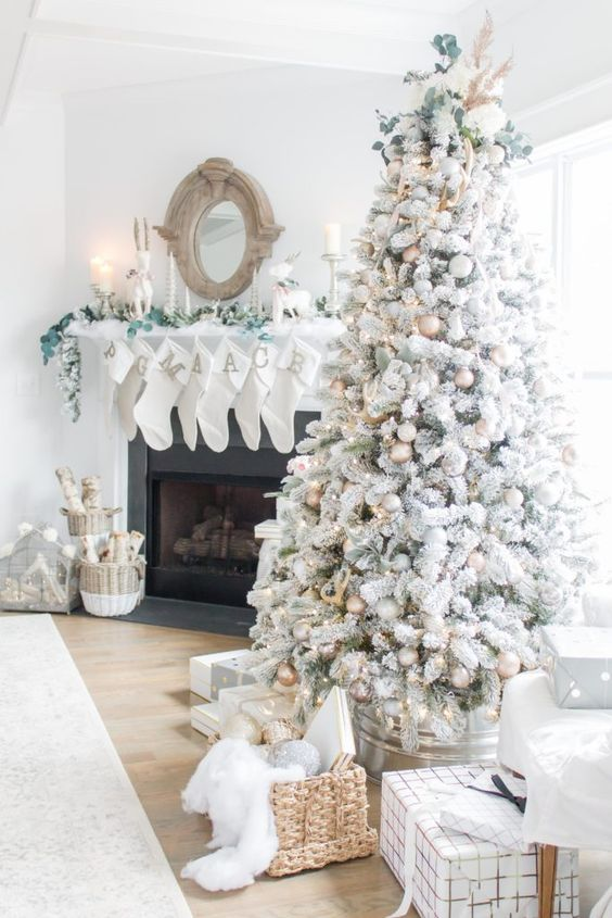 a neutral living room with a flocked Christmas tree with metallic ornaments,  a basket with gifts, white stockings with monogram, greenery and baskets with firewood
