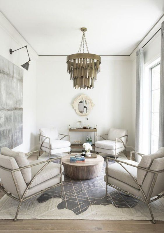 a small sitting space done in neutrals and spruced up with a printed rug, artwork and a bold chandelier