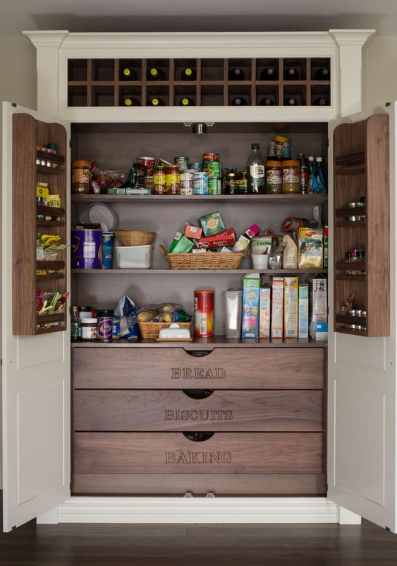 a stylish built in pantry with neutral doors and darker stained built ins   shelves, drawers and built in shelves