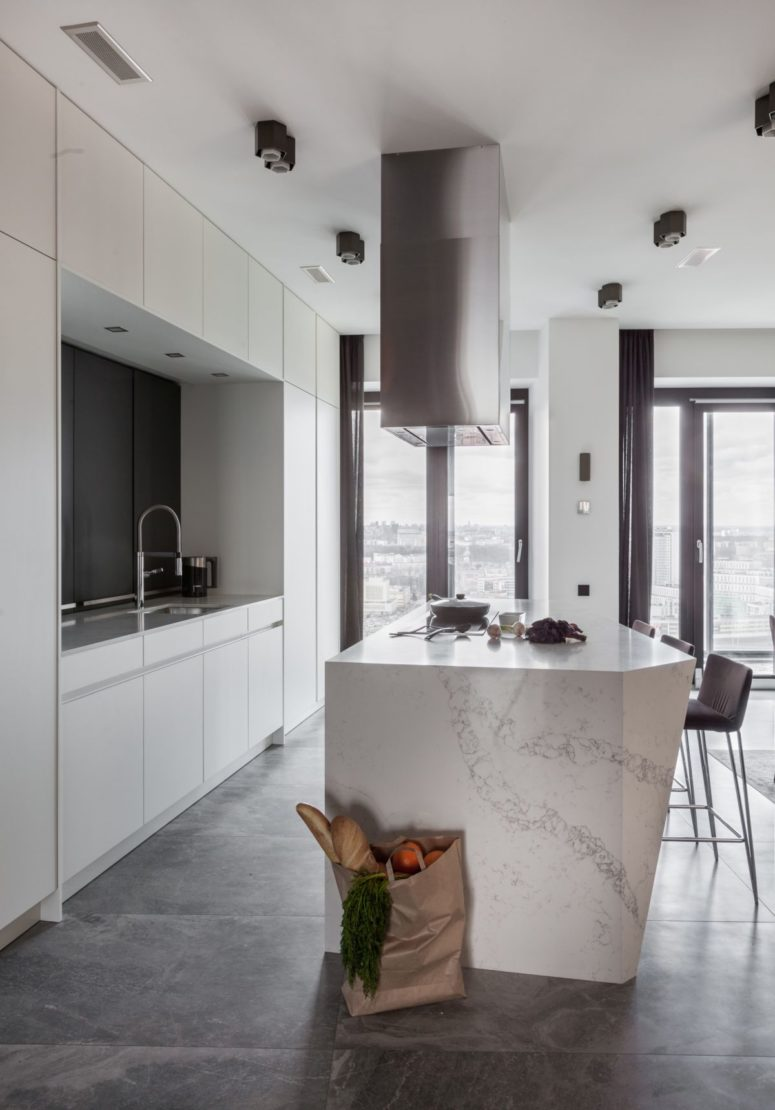 The kitchen is all-white with a marble kitchen island and a glazed wall fills the space with natural light