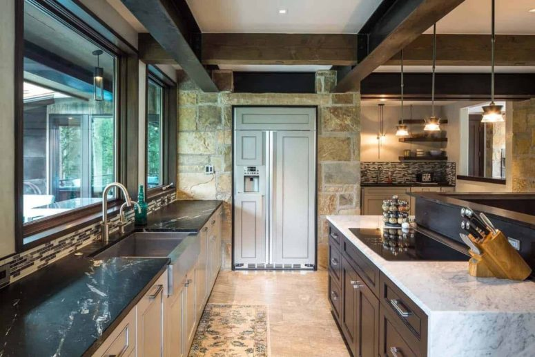 The kitchen is done with white cabinets and black stone countertops, there are stone walls