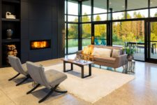 04 The living room is done with a built-in fireplace, a glazed wall and some stylish furniture