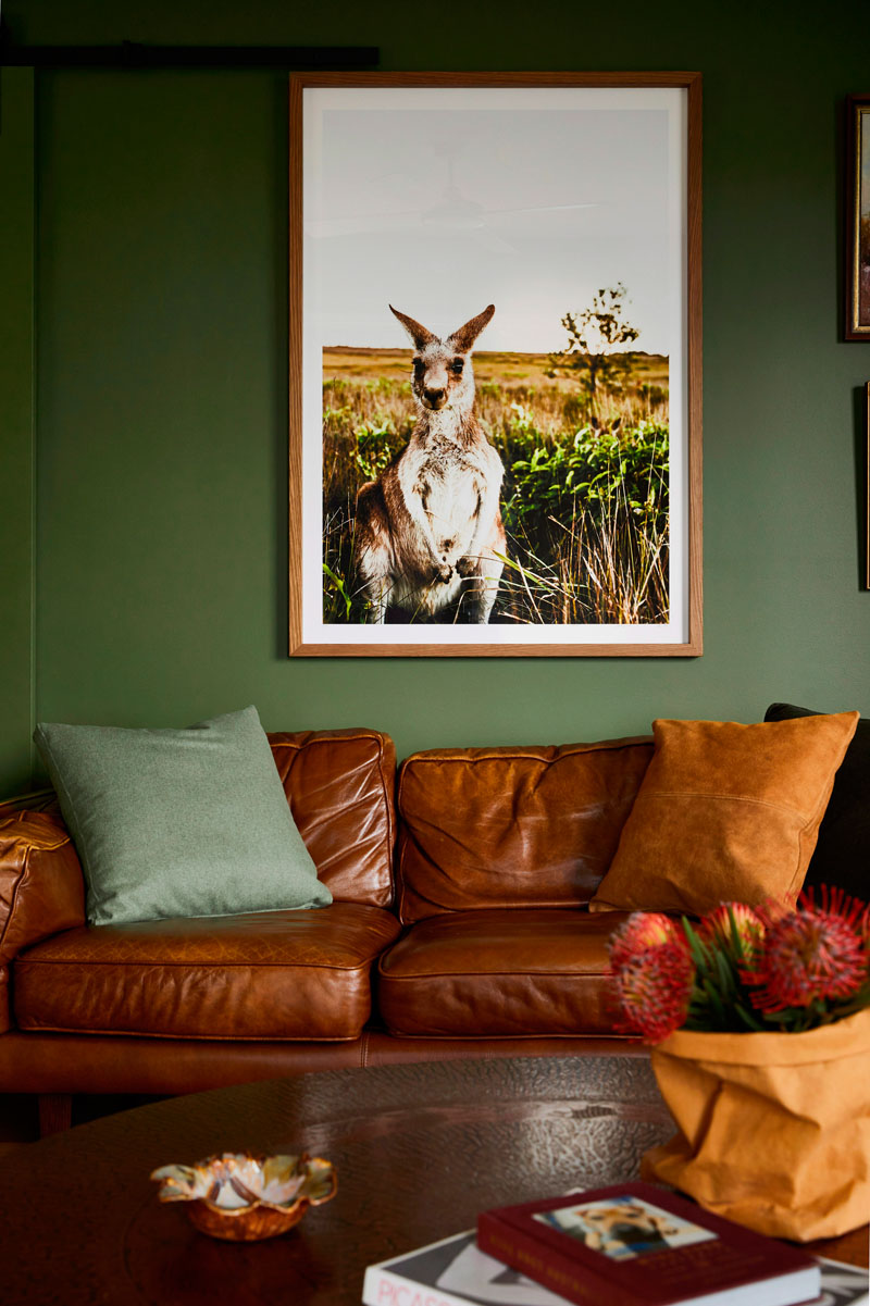 The living room is done with green walls, a brown leather sofa, a rich toned wooden table and a bold artwork