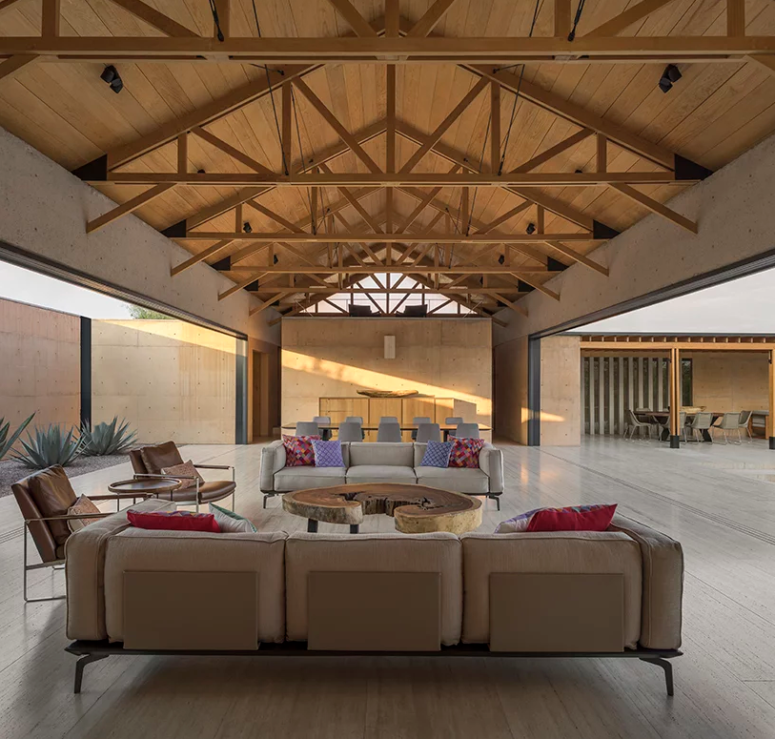 The living space is united with the dining one, there are beams on the ceiling and contemporary furniture with bright touches, sliding doors open the indoor spaces to outdoors