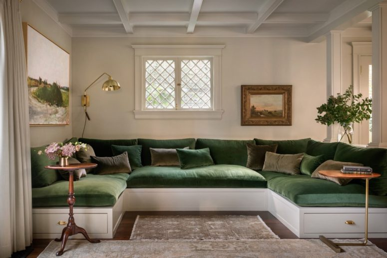 This is a chic conversation zone with a U-shaped sofa and brass touches that features greens