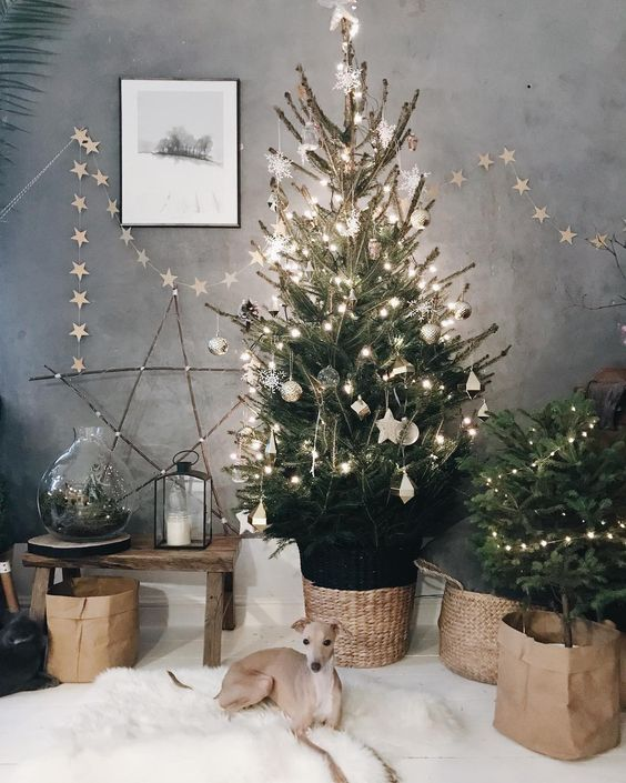 a Christmas tree with lights, white ornaments, baskets, a star garland and a star of twigs