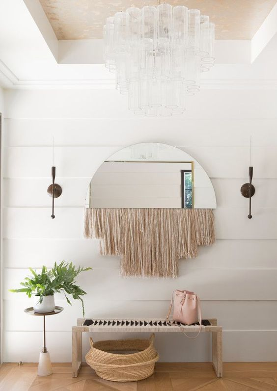 a half circle mirror with long blush fringe is a cool idea for a boho entryway like this one