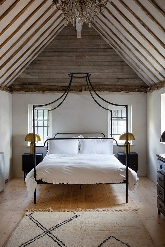 a quirky canopy bed in black on tall legs is a great idea for an eclectic room like this one