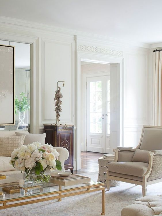 a super elegant neutral living room with chic furniture, an elegant table and a dark cabinet for a colorful touch