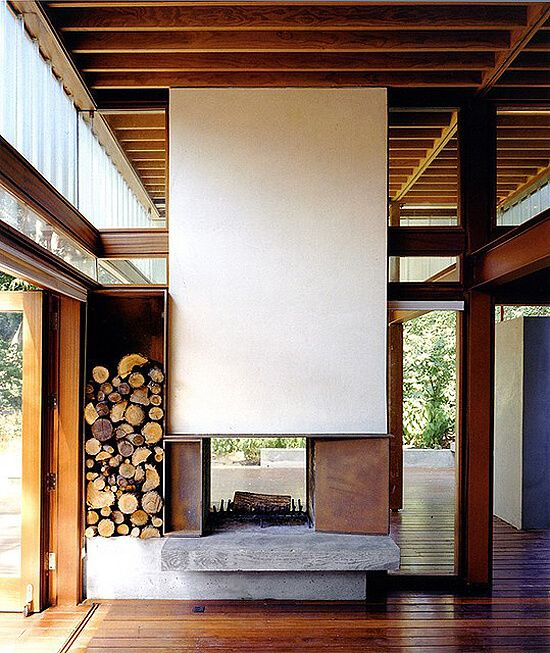 an ultra-modern double-sided fireplace with a white panel over it and metal parts plus firewood stored next to it