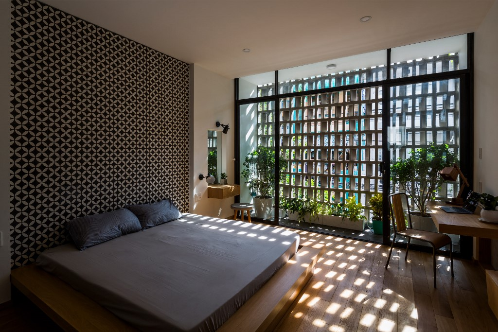 The bedroom features a printed wall, a platform bed and shades on the window plus much greenery