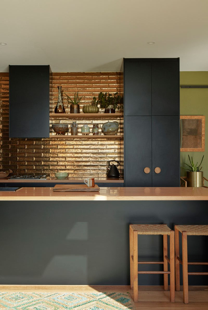 The kitchen features a shiny metallic backsplash and wooden handles to create a contrast with dark furniture
