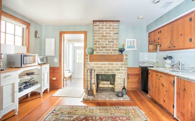 The kitchen is done with rich stained cabinets, light blue walls and backsplashes, a fireplace that is working