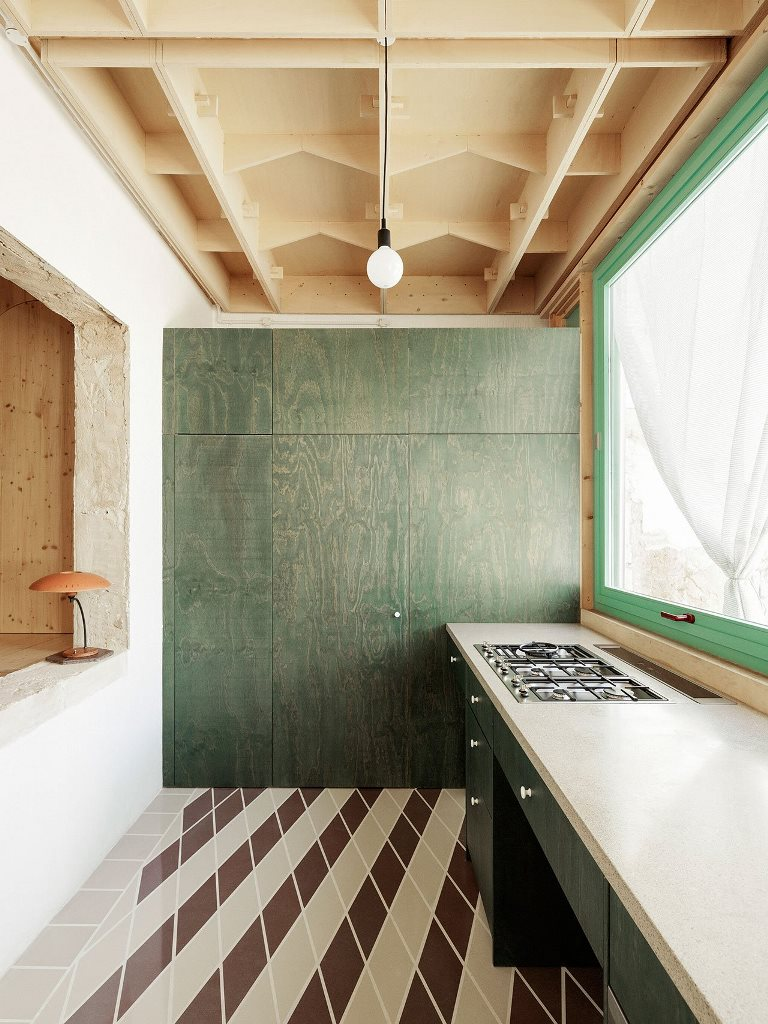 The kitchen is done with tiles and dark green plywood cabinets and a large kitchen island