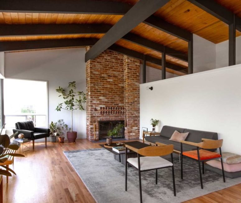 The living room is done with a brick fireplace, pastel and dark furniture and potted greenery