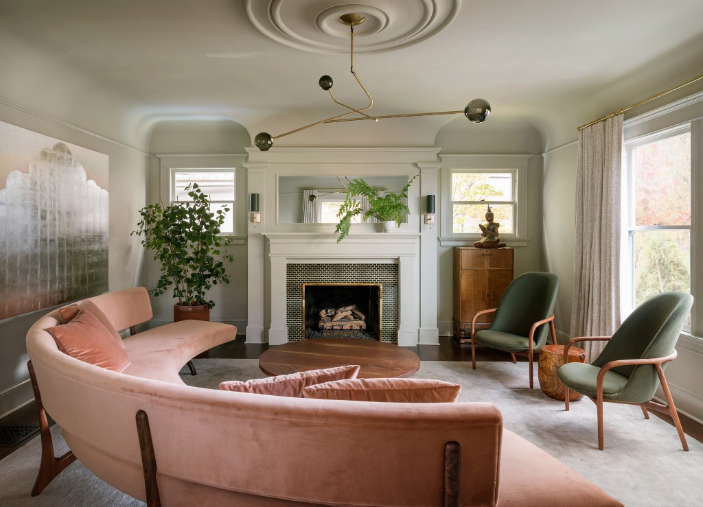 The living room is done with pink and green furniture, a built in fireplace and greenery in pots