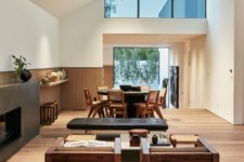 05 The social area features a dining space by the entrance to the courtyard and a living room with a sleek fireplace