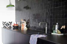 05 a black glazed tile backsplash, stone countertops and sleek black cabinets plus green wall lamps