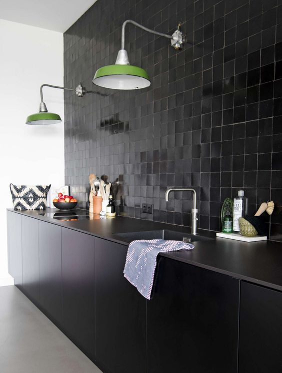 a black glazed tile backsplash, stone countertops and sleek black cabinets plus green wall lamps