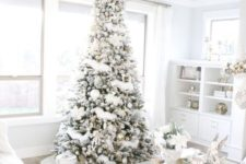 05 a flocked Christmas tree with metallic and white ornaments and lots of gift boxes in white around