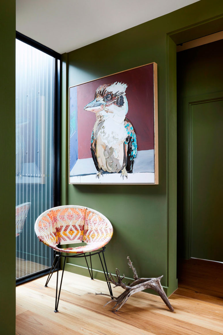Green used for walls is rather muted to make the space feel more like nature, there's a colorful chair and a bold statement artwork