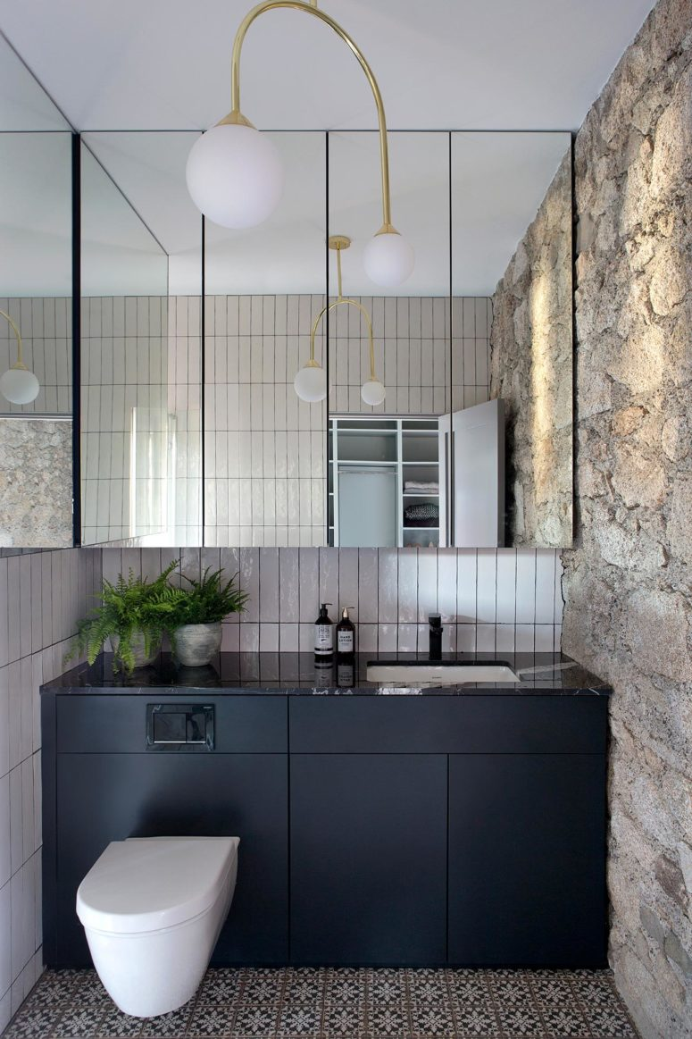 The bathroom is done with a dark sleek vanity, mirrors and a printed tile floor