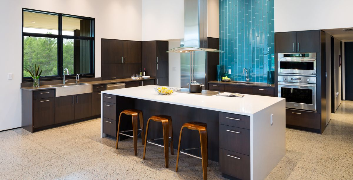 The kitchen is done with dakr furniture, white countertops and a blue tile backsplash
