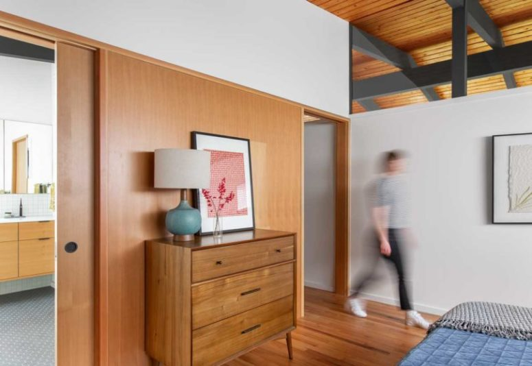 The master bedroom is decorated simply, with stylish mid-century modern furniture and blue textiles