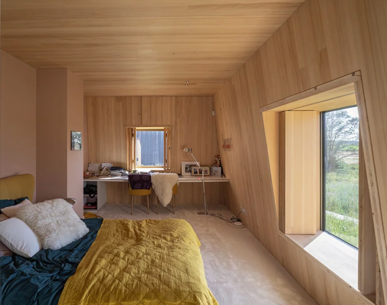 This bedroom is done with plywood completely, there are large windows, a mini home office in the corner and a large bed