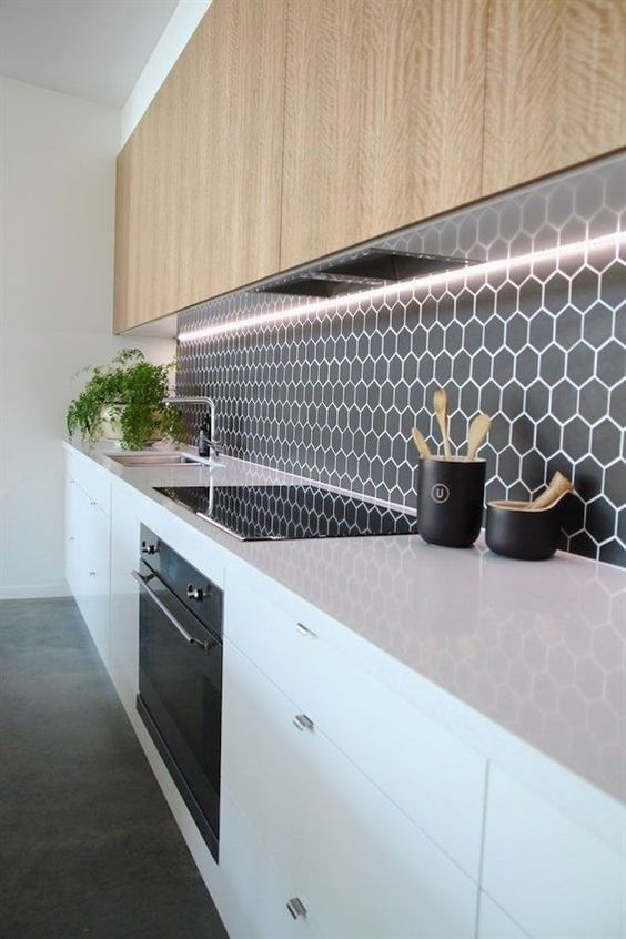 a minimalist black backsplash with small hexagon tiles highlighted with white grout