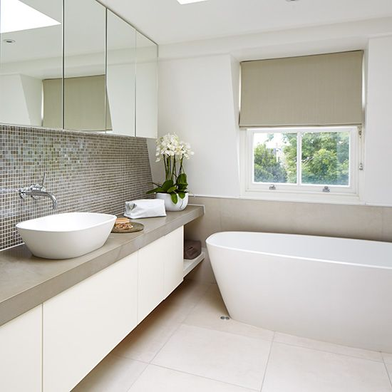a stylish neutral bathroom with grey shades and touches here and there and a grey tile backsplash