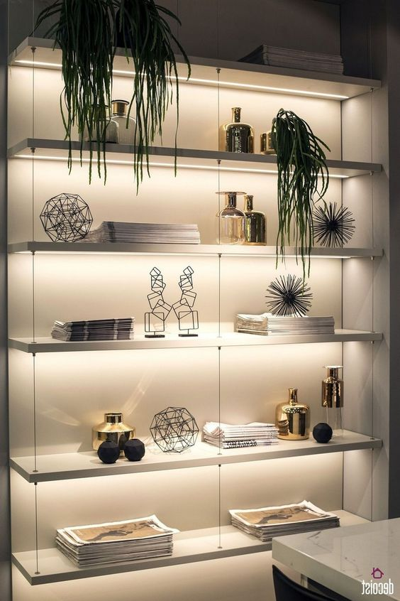 a wall shelving unit lit up with built-in lights is a cool idea to make your objects on display at their best