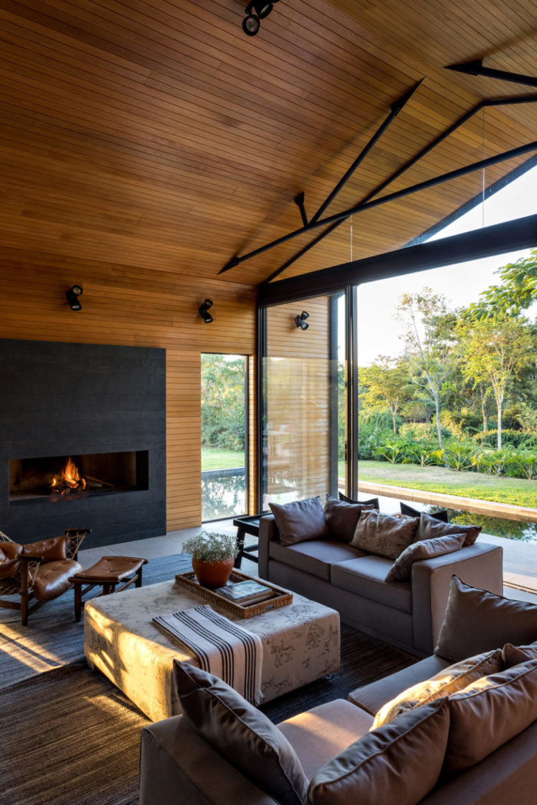 An indoor-outdoor space is done with comfortable furniture and there's a modenr fireplace to create an ambience
