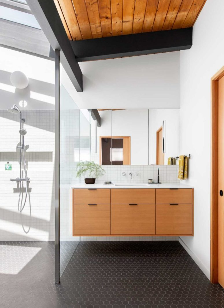 The bathroom features white tiles and black hex ones on the floor, there's a floating vanity