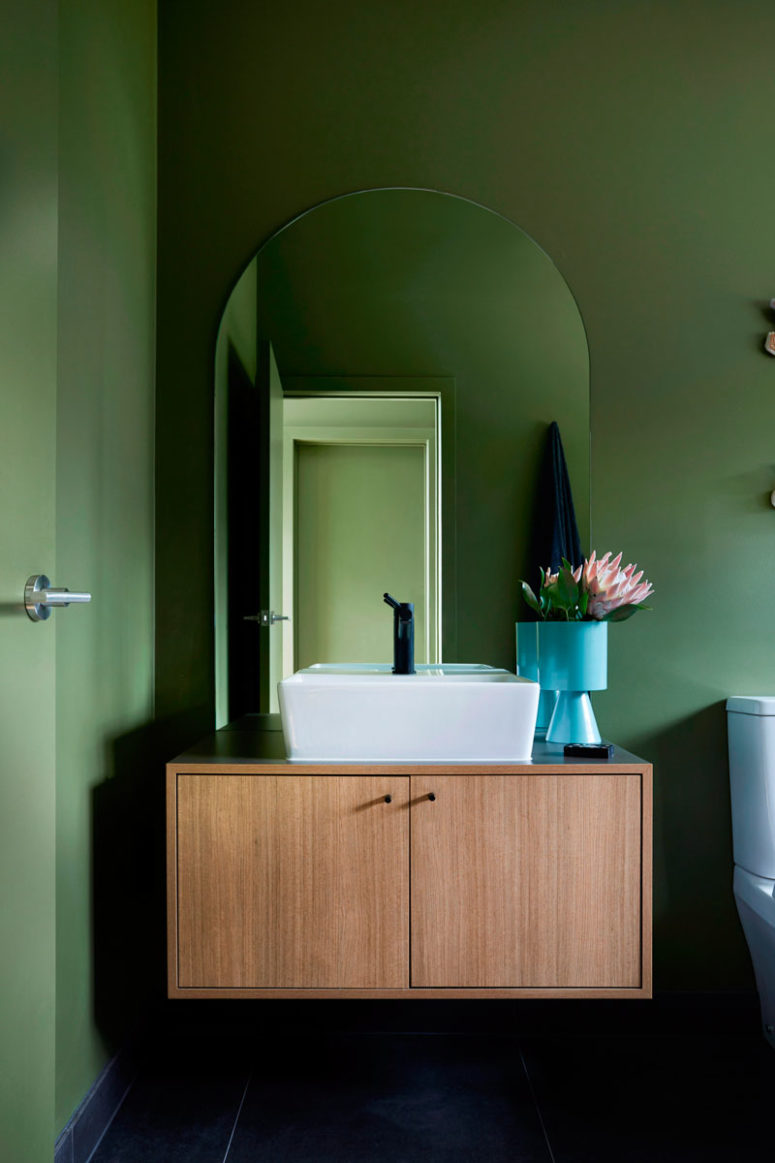 The bathroom is also done with green walls, a floating vanity and a square sink plus dark fixtures