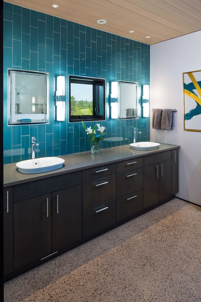 The bathroom is done with dark furniture and blue tiles to connect it to the kitchen