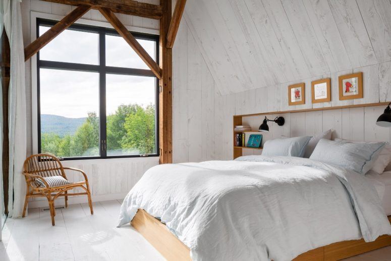 The bedroom features a built-in headboard, a bed, some floatign shelves and a large window