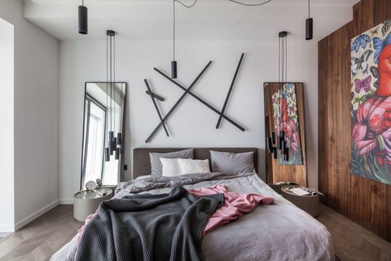 The bedroom is modern and whimsy, wih a bed, a creative artwork, pendant lamps, mini nightstands and a mirror