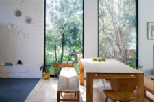 07 The dining zone is placed by the windows to enjoy the views, there's a brick wall and a sile wooden furniture set