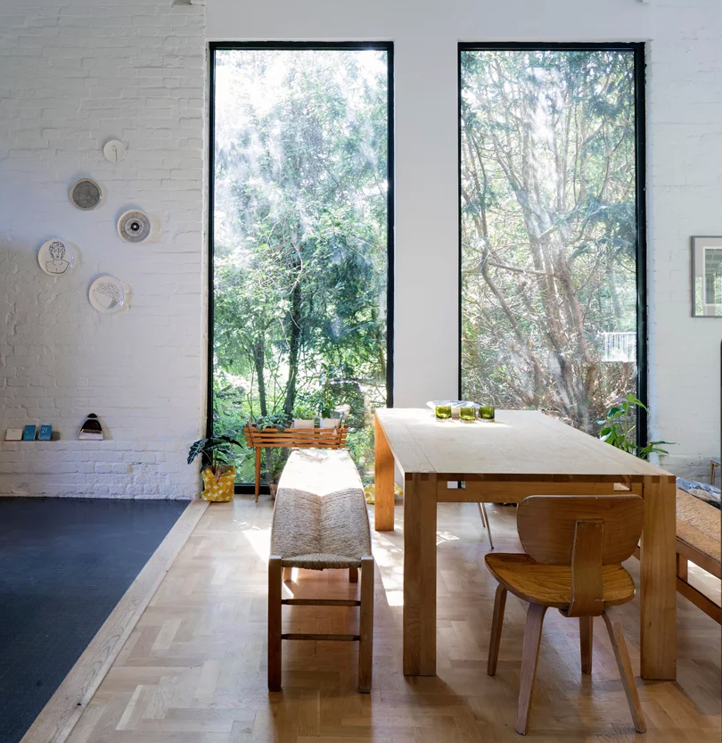 The dining zone is placed by the windows to enjoy the views, there's a brick wall and a sile wooden furniture set