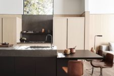 07 The kitchen is done with sleek light-colored cabinets, a dark kitchen island and brown chairs