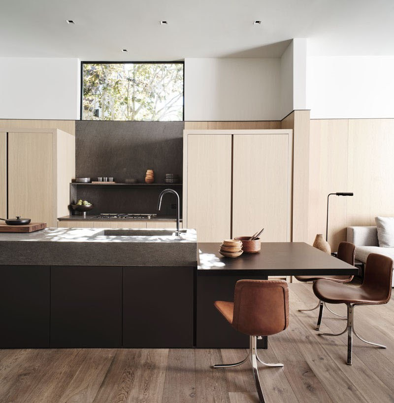 The kitchen is done with sleek light colored cabinets, a dark kitchen island and brown chairs