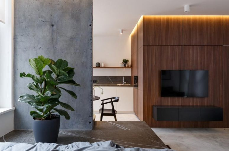 The wood clad wall features a floatign cabinet and a TV