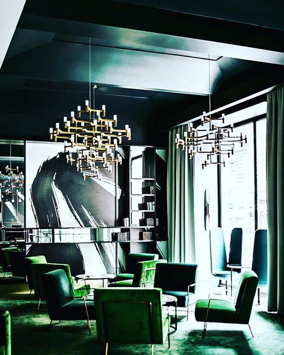 a chic opulent space done in greens and teal, with statement chandeliers and comfy furniture
