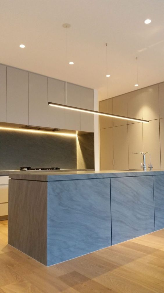 a minimalist kitchen with sleek cabinets and lots of built-in lights looks very chic and very edgy